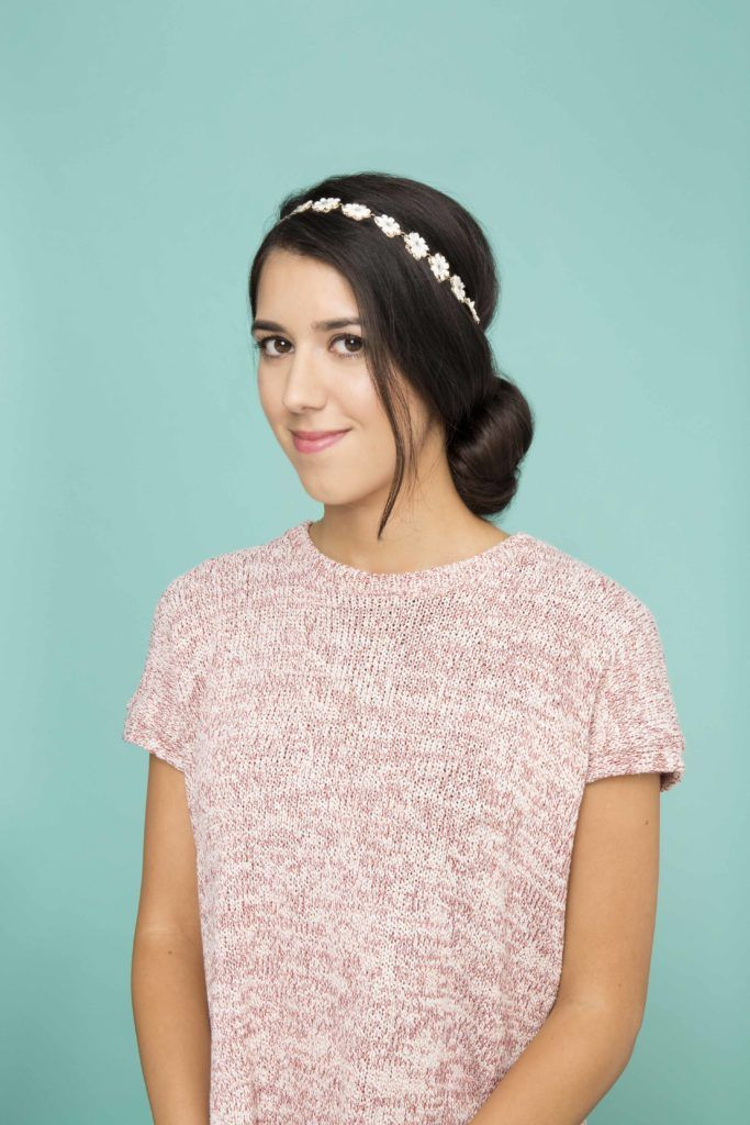 woman looking at the with dark brown hair styled into a low bun with a headband accessory attached wearing a pink top