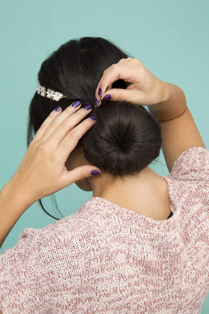 back view of a woman with dark brown hair styled into a low bun with a headband accessory putting in a hair pin and wearing a pink top
