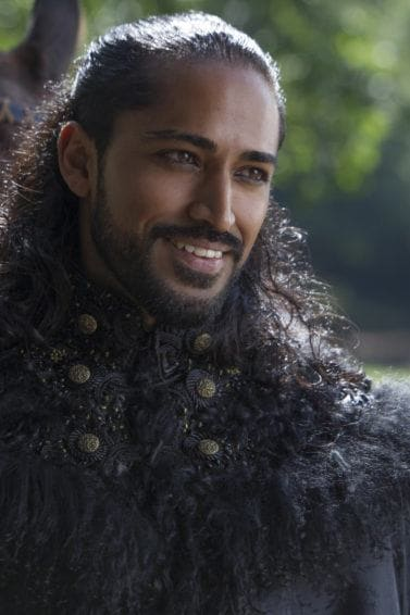 man with long dark hair and a beard worn in a half-up hairstyles