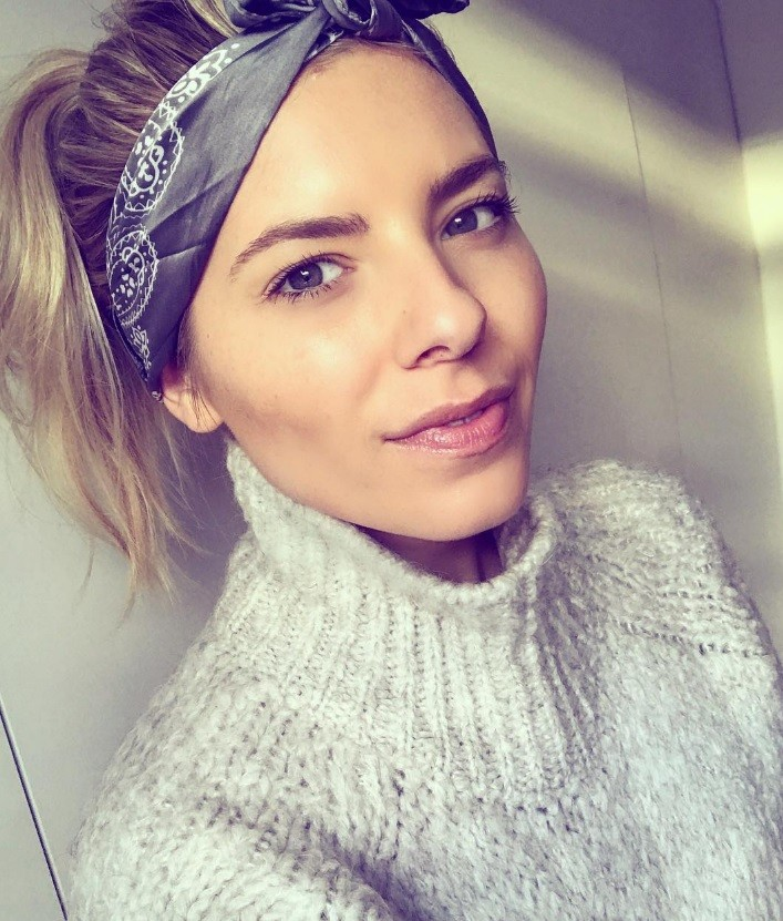 Mollie King wearing a printed bandana in her blonde hair styled into a high ponytail wearing a light grey sweater