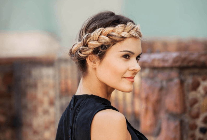 party hair ideas: side view of a woman's head with blonde with a halo braid