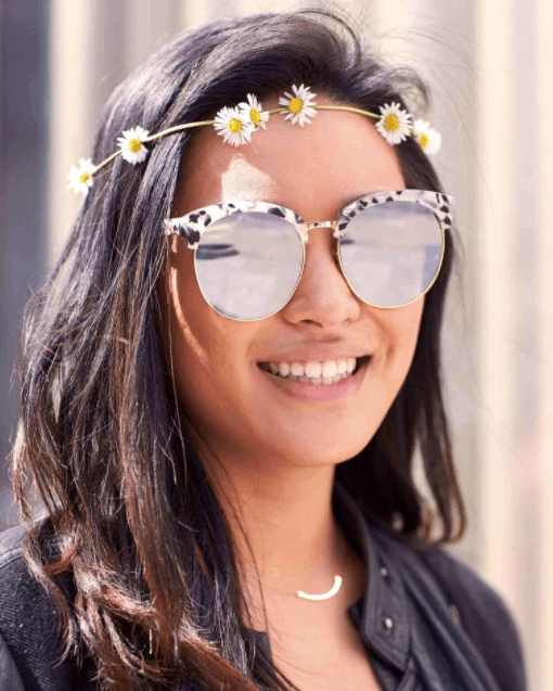 hairstyles for a party: front facing image of a woman with sunglass on and dark wavy hair with flowers in her hair
