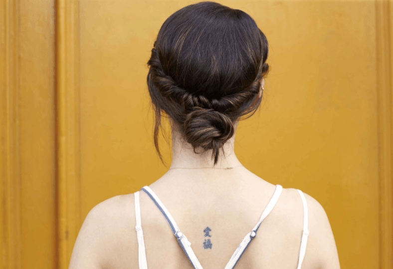 hairstyles for a party: back view of a woman's head with dark hair and a low twisted bun