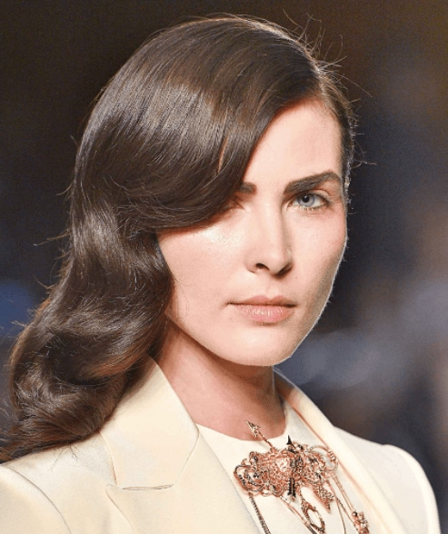 evening hairstyles: front facing image of a woman with dark brushed out waves