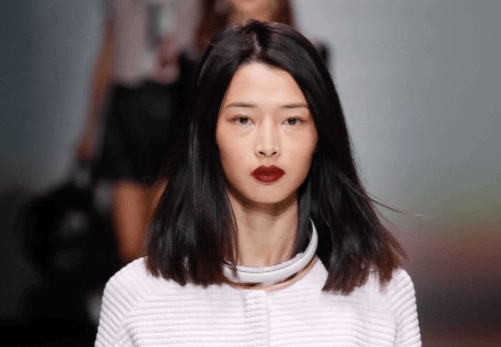 front facing image of a woman with black hair in a middle parting