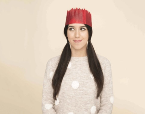 Christmas hairstyles: Woman with long dark hair in pigtails, wearing a Christmas hat and a spotted knitted jumper.