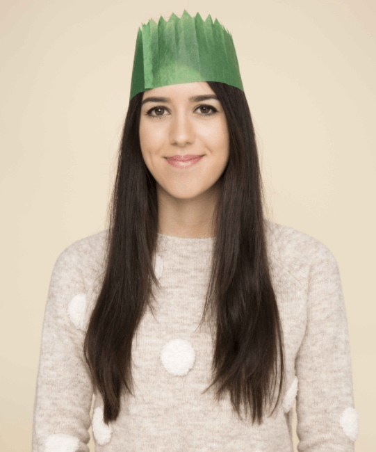 Christmas hairstyles: Brunette woman with long straight brown hair wearing a green party hat and spotted knitted jumper.