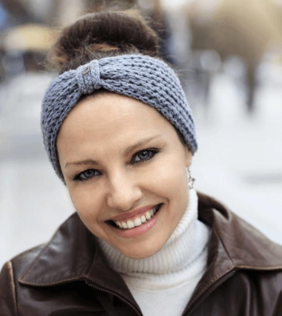 Christmas hairstyles: Woman with brown hair in bun updo with grey knitted headband wearing a turtleneck white top.