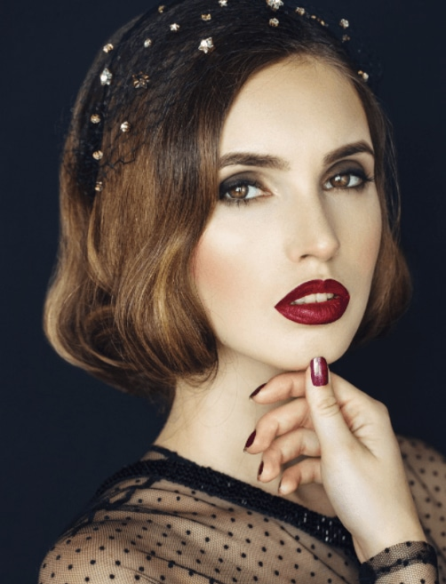 Christmas hairstyles: Woman with brown hair styled with soft waves and a jewelled hair net wearing red lipstick touching her chin.