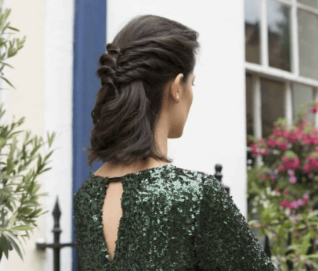 Christmas hairstyles: Woman with wavy brown hair in half-up twisted style wearing a green glitter dress.