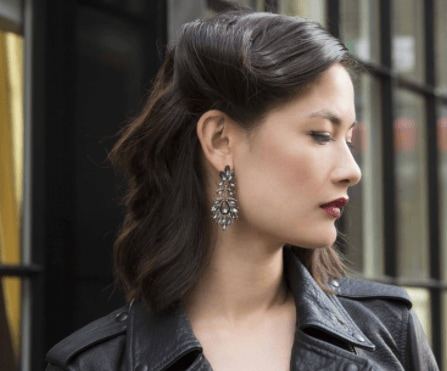 Christmas hairstyles: Woman with dark brown hair in vintage retro glam roll wearing a black leather jacket and jewelled earrings.
