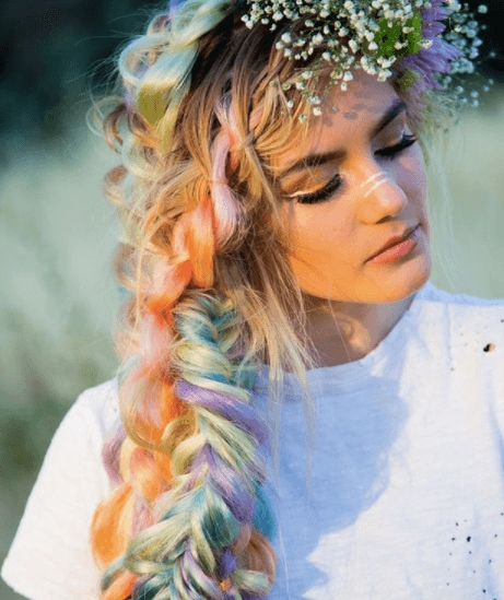 Fishtail braids: Woman with blonde colourful hair with a fishtail hairstyle and flowers in her hair