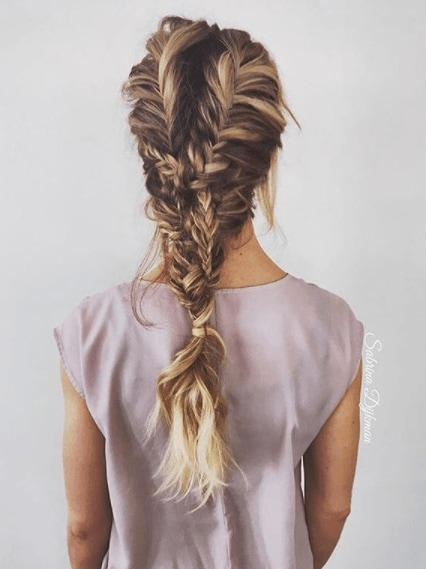 Fishtail braids: Woman with long dark blonde highlighted hair in a fishtail hairstyle updo.