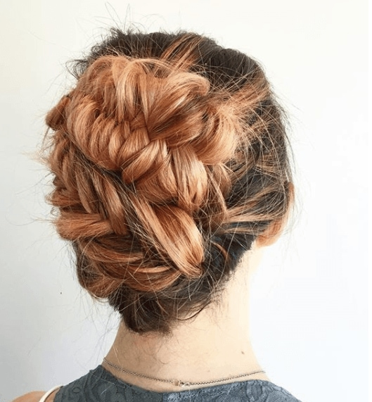 Fishtail braids: Woman with brown hair with peach balayage styled in a fishtail hairstyle updo