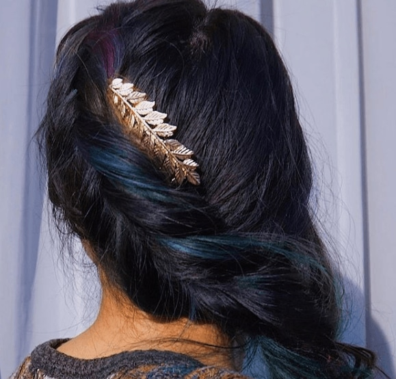 Fishtail braids: Woman with dark brown hair in a long fishtail hairstyle with a gold leaf hair clip.