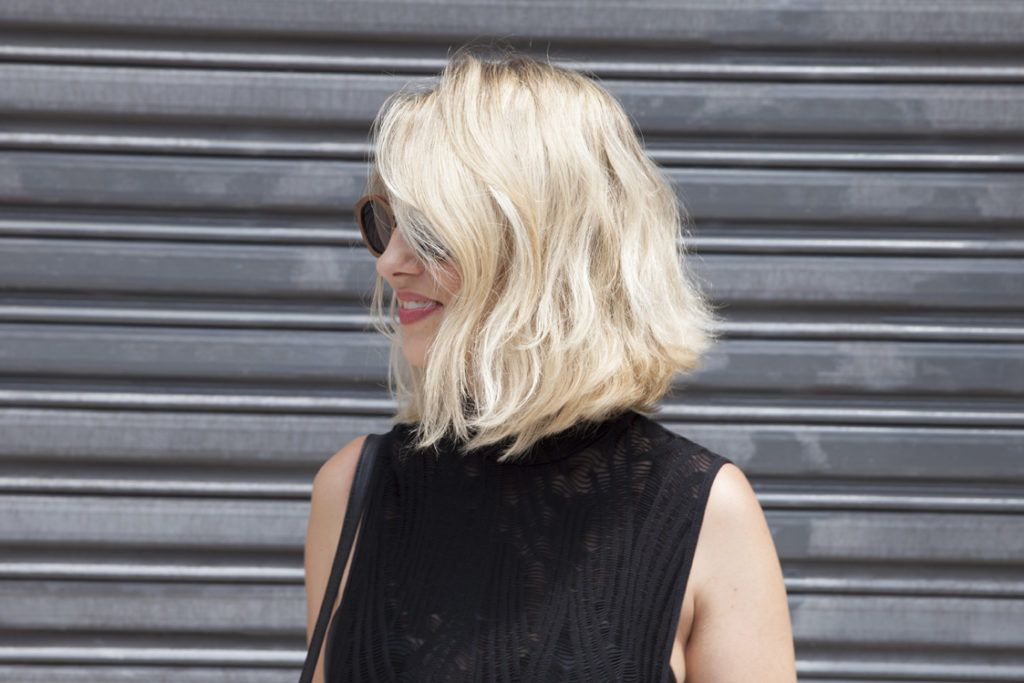 naturally wavy hair: street style shot of woman with tousled blonde bob, wearing a black top with a matching handbag, posing against a backdrop