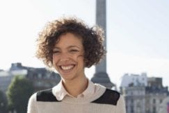 Hairstyles for short curly hair: woman with a short bob deep side parting in her brown curly hair