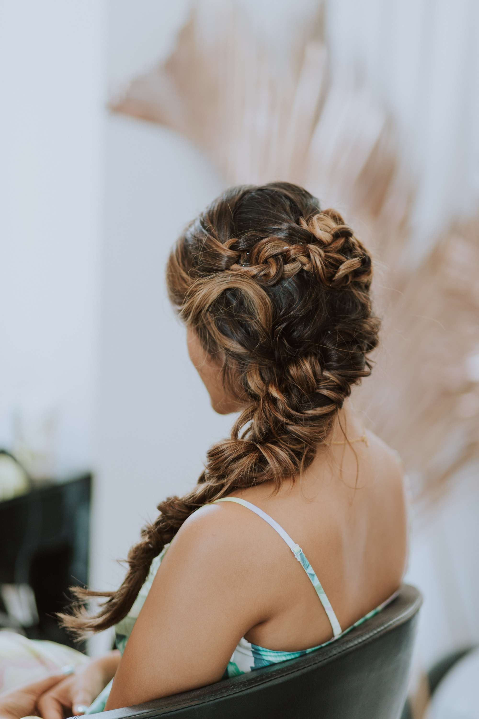 natural wavy hair: close up shot of woman from behind with a wavy intricate side braid, wearing a floral print spaghetti top and sitting in a chair