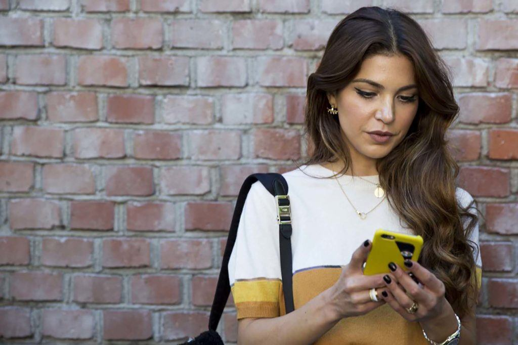 naturally wavy hair: close up shot of woman with side swept dark brown waves, wearing white and gold top, posing against a brick wall and holding a phone