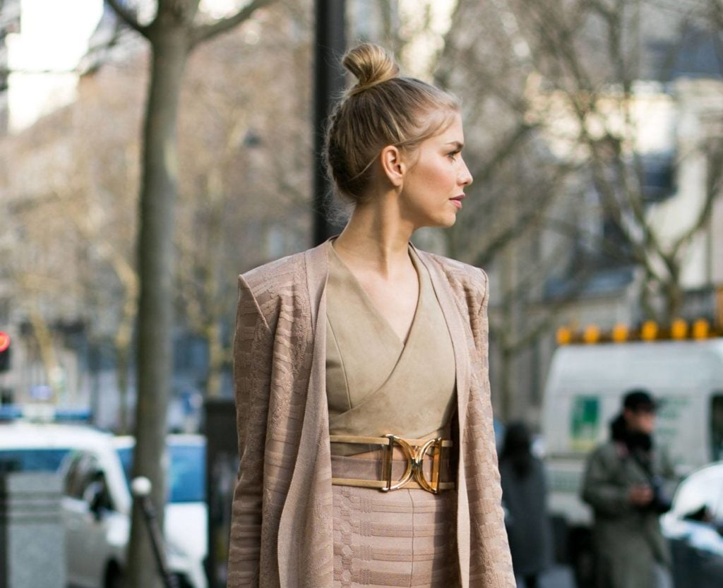 woman on the street with her golden brown hair styled into a high bun hairstyle