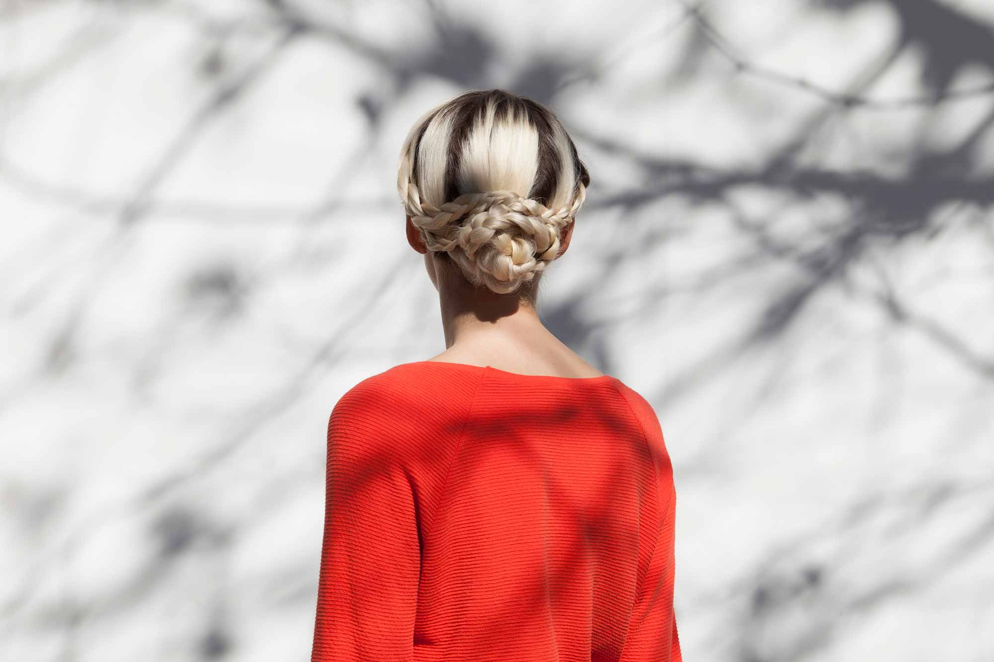 back shot of a blonde woman with her hair in a low braided snake bun wearing a red top