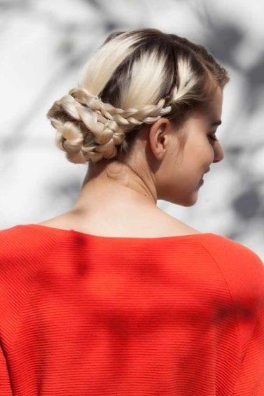 Easy plait hairstyles: blonde woman with dark roots with a snake braid hair bun