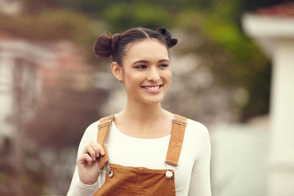 Hair for a party: front facing image of a woman with dark hair in two space buns