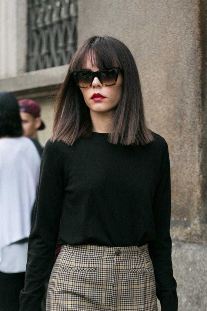 woman with sleek and blunt cut long bob hairstyle on brunette hair wearing a black sweater