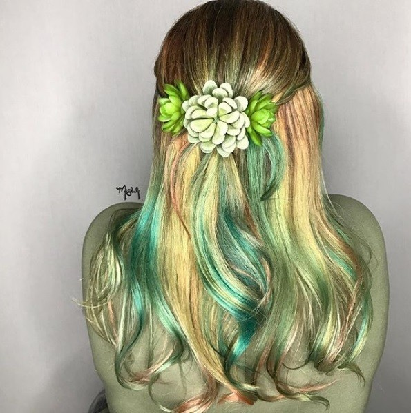 back view of a woman with long wavy green and golden blonde hair styled in a half up half down with succulent hair accessories