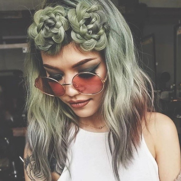 woman with shoulder length wavy green succulent hair with braided space buns wearing red circular sunglasses
