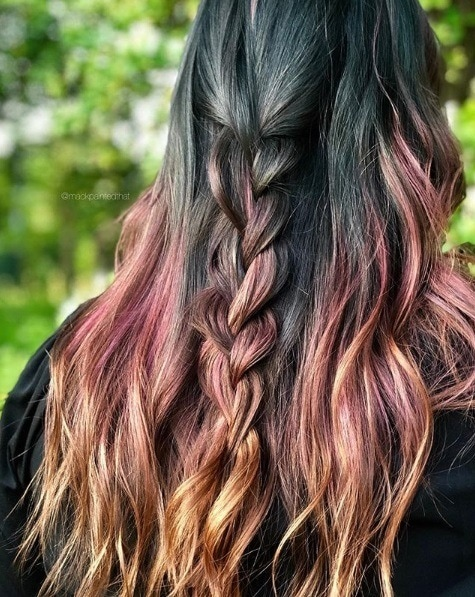 back view of a woman with long wavy hair in a teal pink and orange colour melt with a half-up half-down braid