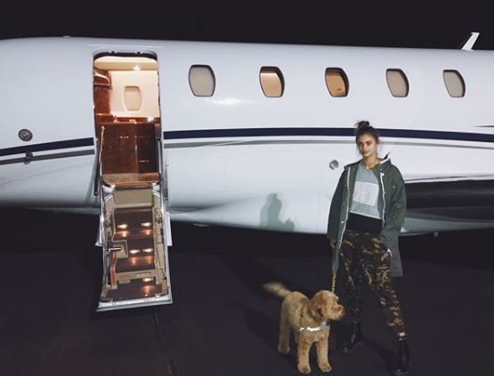 front view of taylor hill with brown hair in high messy bun in front of plane with dog
