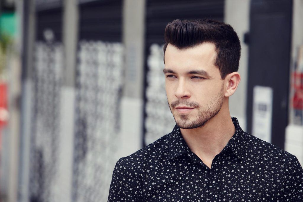 man with dark brown hair worn in a textured quiff hairstyle wearing a spotted shirt