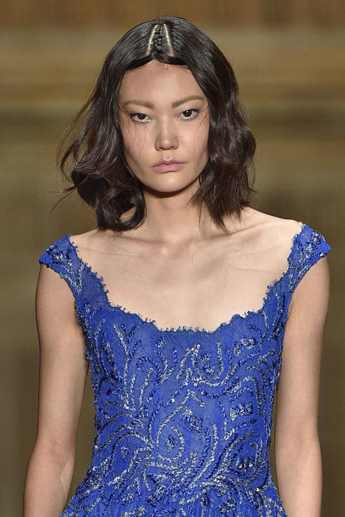 model with brown wavy bob on the runway wearing a blue dress
