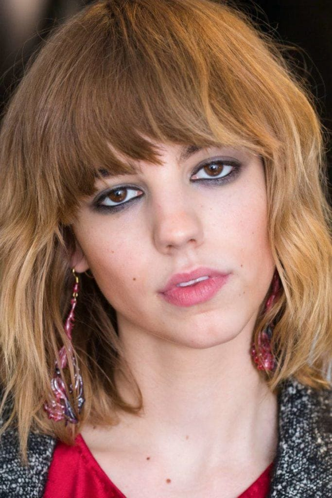 party hair ideas front facing image of a model with a fringe and tousled waves