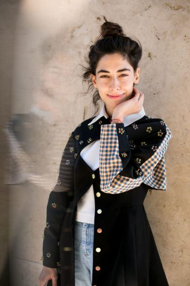 natural wavy hair: close up shot of dark haired street style model with wavy topknot, wearing black jacket and denim dress, and posing on the street