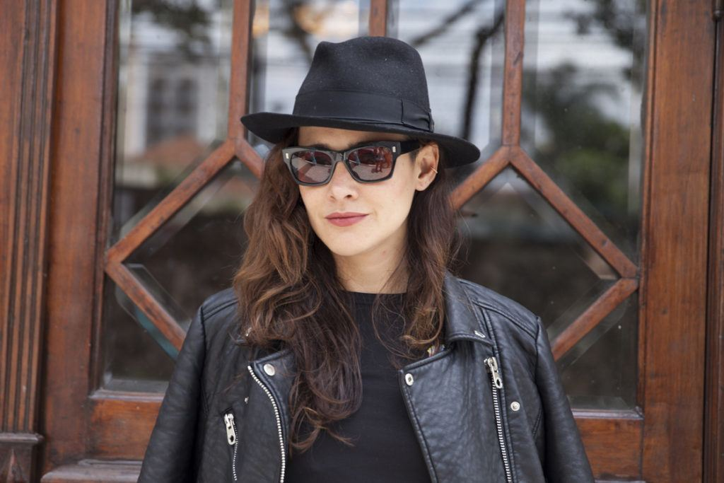 naturally wavy hair: close up shot of a brunette woman with wavy hair and a trilby hat, wearing sunglasses and a black outfit, posing against a window