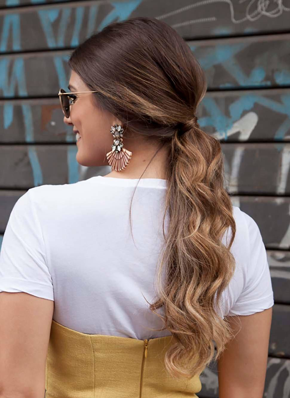 natural wavy hair: back shot of woman with naturally wavy caramel coloured hair styled into a low ponytail, wearing white and posing on the street