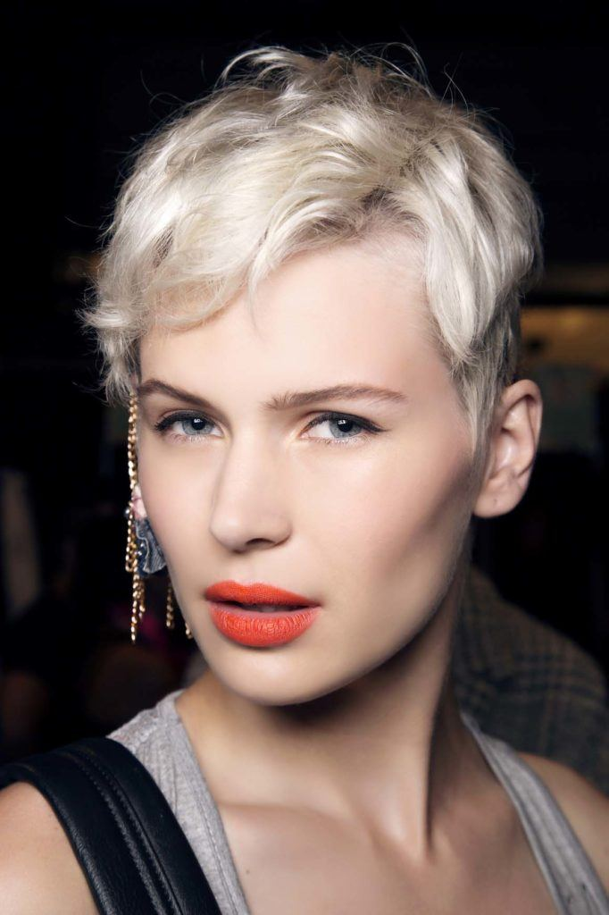 model with platinum blonde pixie hair parted down the side, wearing red lipstick