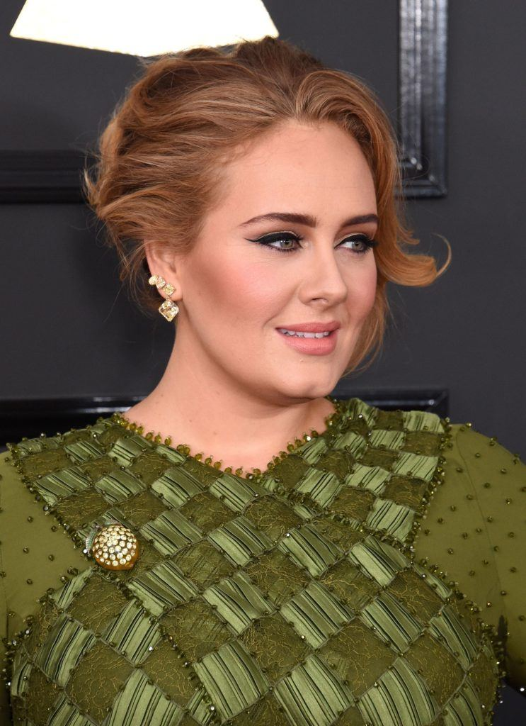 Close up shot of Adele with light brown hair styled into a chic updo with loose tendrils