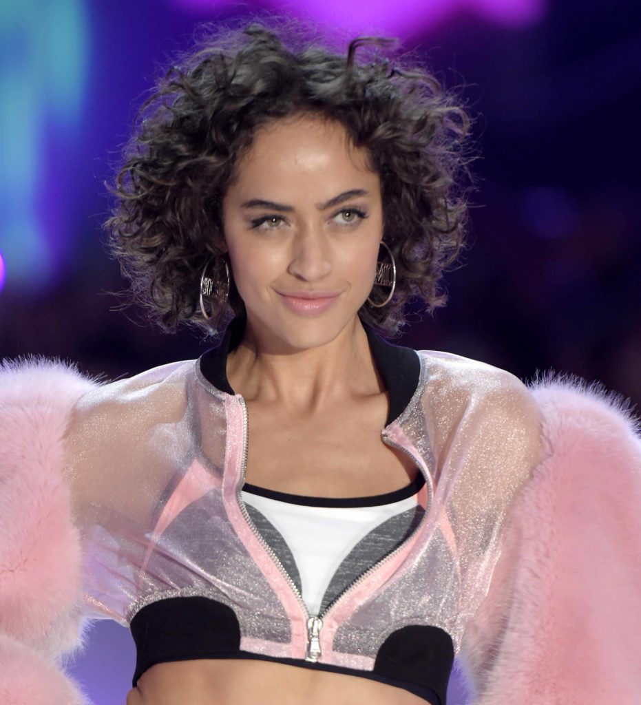 Alanna Arrington on the runway of the Victoria's Secret show with short curly hair