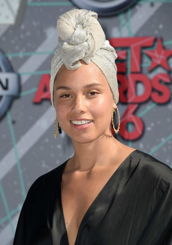 Alicia Keys wearing a white silk headwrap and black dress in the red carpet