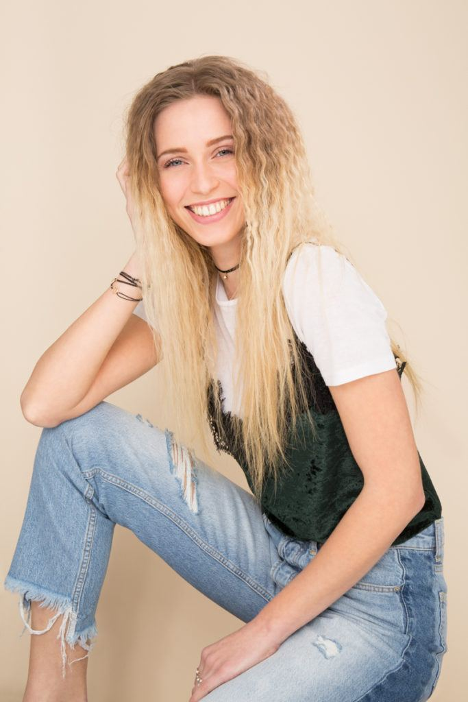 '80s hairstyles:blonde model with long hair styled in a modern crimped hairstyle wearing jeans and top in studio