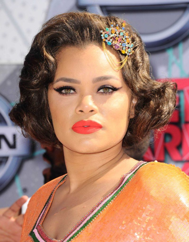 Andra Day with a wavy bob wearing a jewelled hair clip and an orange dress on the red carpet