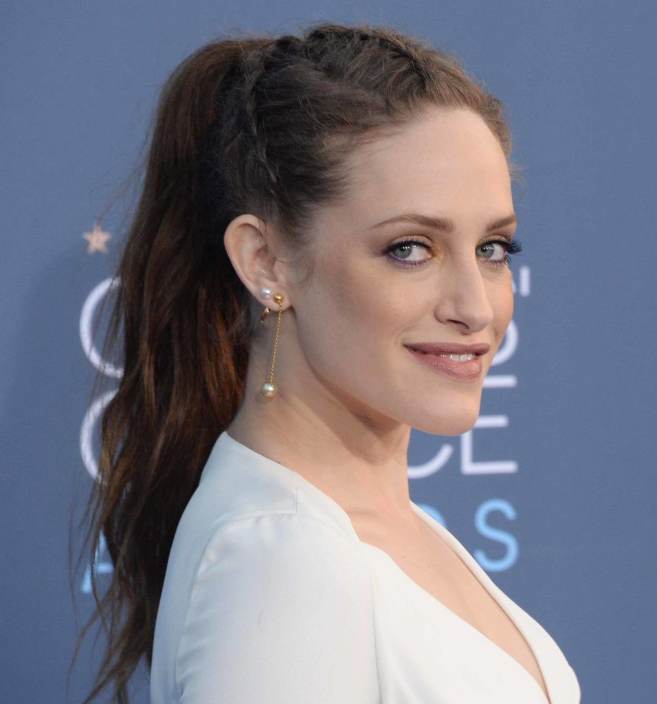 Carly Chaikin on the red carpet with her dark brown hair styled into a ponytail with cornrows