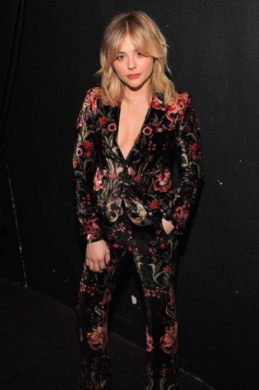 actress chloe grace moretz in a velvet floral baroque suit with mick jagger inspired 70s blonde bangs