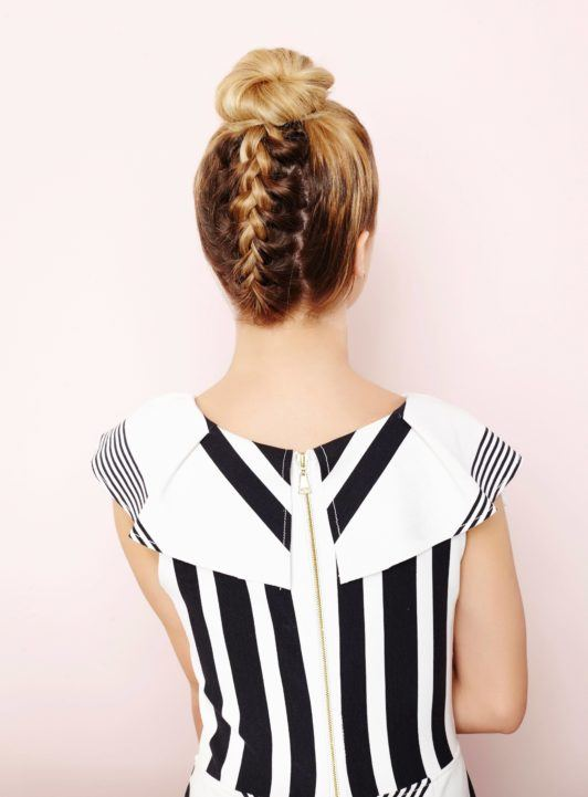 How to do an upside down Frnech braid: the back view of a young blonde womand with the final look