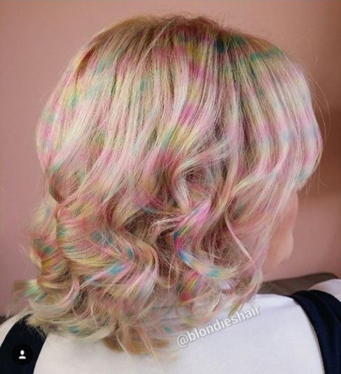 side profile of a woman with bob length curly blonde hair with pastel coloured confetti dye