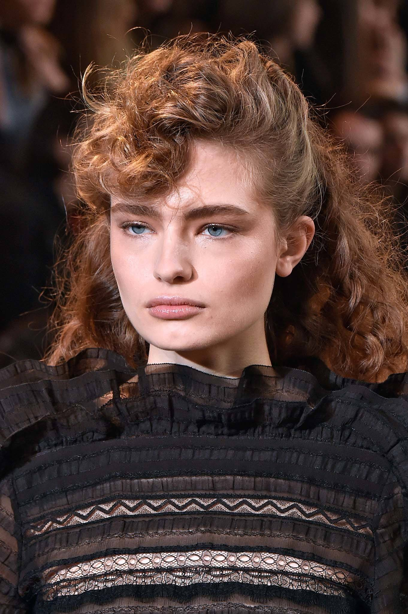 Retro hairstyles: Close up shot of a woman with light brown naturally curly hair styled into fauxhawk walking on the Isabel Marant runway