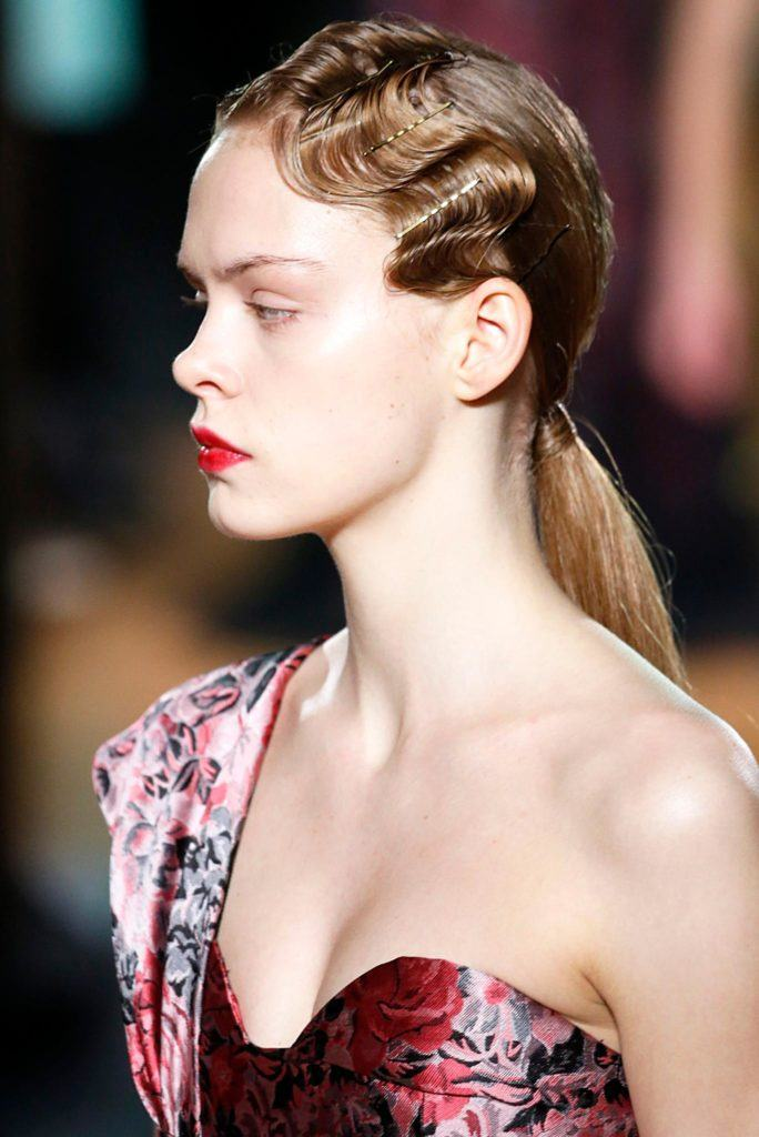 Retro hairstyles: Close up side shot of a model with dark blonde hair styled into a low ponytail with finger waves detailing. complete with bobby pins, wearing pink on Erdem runway